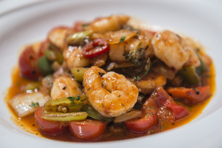 Seafood and vegetable stew in tomato sauce served on white plate Stock Photo