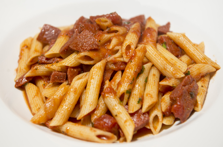 diced: Penne with diced meat and tomato sauce on a white plate