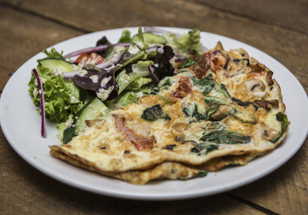 Omelette with mashrooms, bacon and vegetables served with salad Stock Photo
