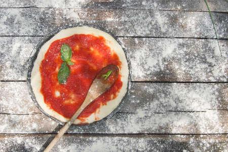 pizza base: Preparing pizza made with tomato basil and mozzarella
