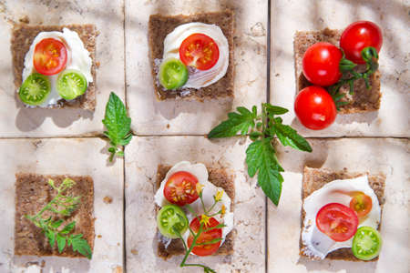 Presentation of slices of wholemeal bread with cheese and cherry tomatoes
