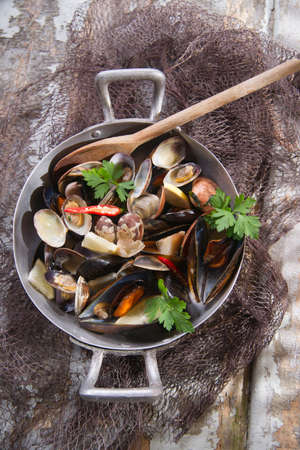 Preparing a soup made from seafood with garlic and parsley