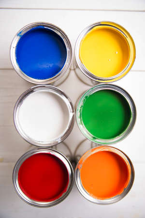 red wall: Presentation of a series of cans of paint of various colors Stock Photo