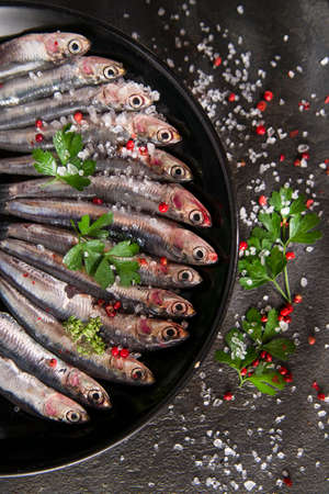 edible fish: Presentation of a dish of raw anchovies on black background