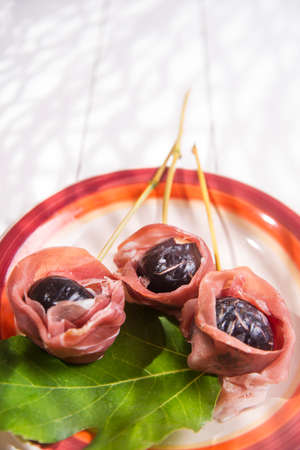 blacks: Presentation of dish skewers with ham and figs blacks