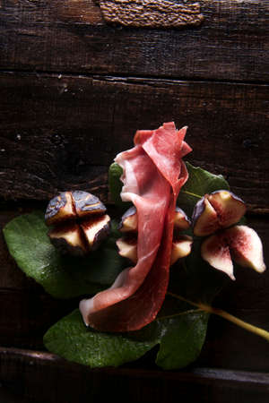 blacks: Presentation of skewers with prosciutto and figs blacks