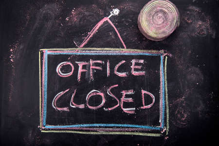 is closed: Graphic representation of the word, office closed, written with chalk on blackboard Stock Photo