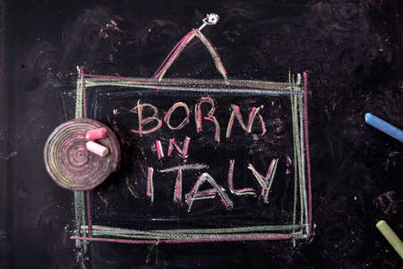 says: Sign indicating that says born in Italy, written with chalk on blackboard