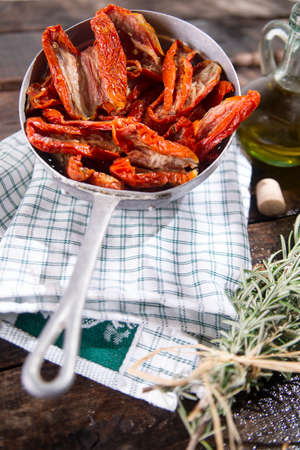 a colander: Presentation portion of dried tomatoes with rosemary in small colander Stock Photo