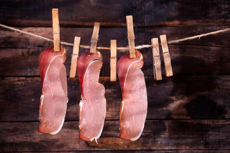 bacon: Presentation of slices of bacon hanging by a thread with tweezers Stock Photo