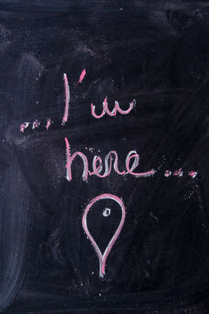 i am here: Graphic representation with chalk on the blackboard of the sentence ... I am here ...