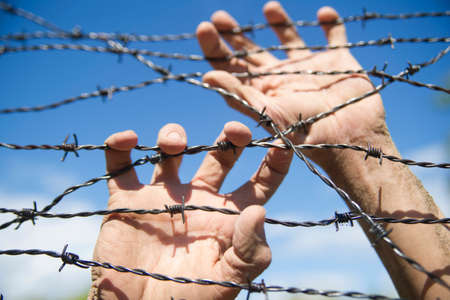 run away: Hands gripping the barbed wire in the sign to run away with the blue sky background