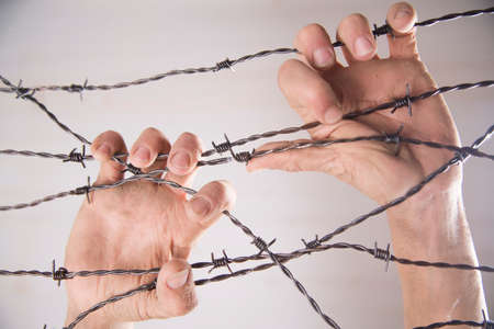 run away: Hands gripping the barbed wire in the sign to run away with the white background