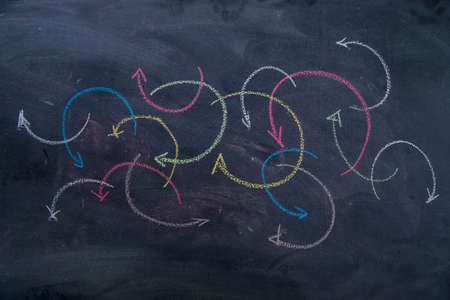 curved arrows: Colorful curved arrows drawn with chalk on blackboard