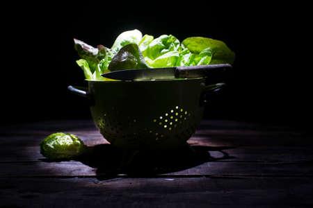 Presentation of a salad basket in a colander or on a black background