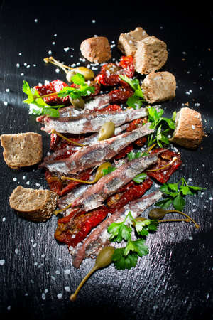 Second dish based on anchovies in salt, dried tomatoes and capers Banco de Imagens