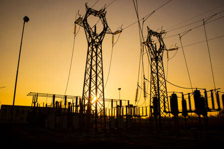Steel pylons in a power plant for the distribution of electricity at sunset Archivio Fotografico