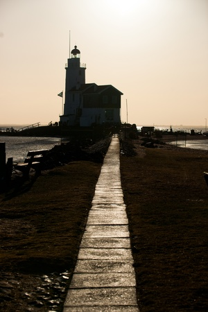 Dutch Lighthouse in the winter picture made against the sunlight photo