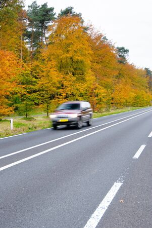 Car driving on country road  Autumn scene, low angle, motion blur