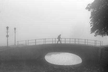 lone hiker on sad morning walk over a bridge