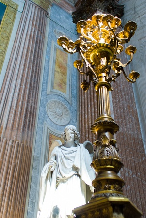 angel and candle, staning in the light at church, italy photo