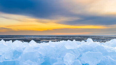 Early morning winter landscape with sunrise and drifting ice floats near costline in the Netherlands photo