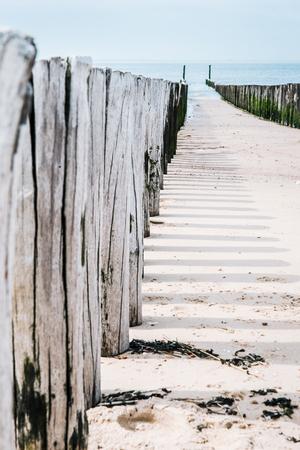 Houten golfbrekers op het strand van de Noordzee, Nederland