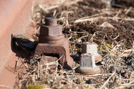 junction pipe: Old and lost Railroadtrack with nut and bolt on background of gravel and moss. Stock Photo