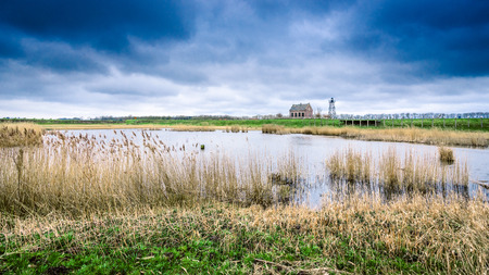 """이전 Zuiderzee 섬의 옛 항구, 네덜란드의 polder에있는 """"Schokland"""". 이것은 방파제, 교각, 부두, 등대지기 집 및 조명 쇼를 재구성 한 것을 보여줍니다."""