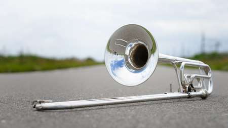 background image: Close up of single silver trombone in an outdoor situation