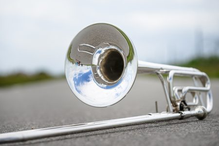 gold metal background: Close up of single silver trombone in an outdoor situation
