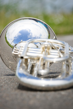 silver background: Close up of a detached silver marching baritone.