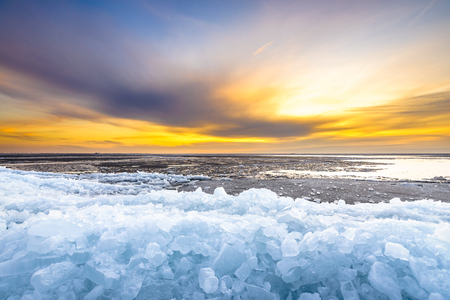 drifting ice: Early morning winter landscape with sunrise and drifting ice floats near costline in the Netherlands