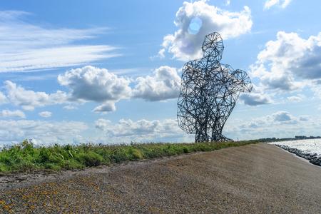 lelystad: Statue of a man sitting on his heels on an enclosure dam in Lelystad, Netherlands