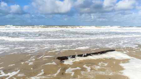 texel: Waves advancing into the beach with lots of foam at the coast. Picture made at the island texel, Netherlands