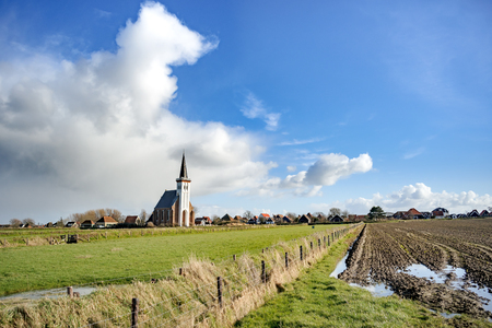 hoorn: Panoramic shot of old Dutch church. Farmland. Stormy cloudy sky. Texel. Den Hoorn. Wadden island. The Netherland Stock Photo