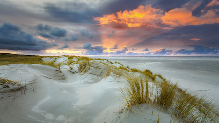 Sunset on the island of Texel with dunes and dune grass with a wide beach below.