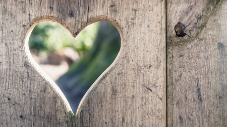 Heart shape cut into wooden boards background with sunshine Stock fotó