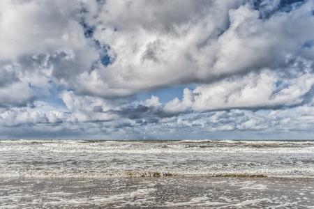 Golven op weg naar het strand met veel schuim aan de kust. Beeld dat bij het eiland texel, Nederland wordt gemaakt