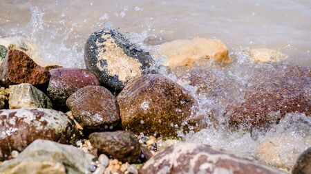 Colorful Rocks with splashing waves. pebble stones by the sea on a beach