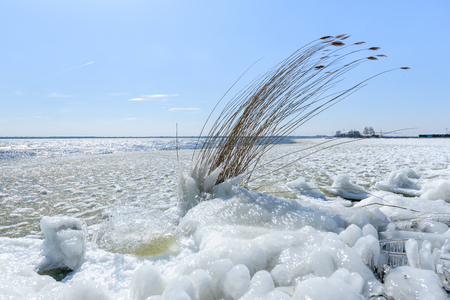 icescape: Natural ice sculpture with a blue sky with clouds in the background