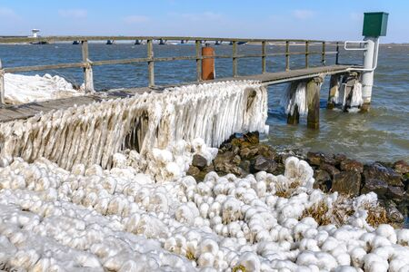 ice storm: Extreme Ice Storm Hits Lake Shore. Thick ice coats the shore of a dutch lake, Netherlands Stock Photo