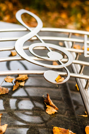 Silver chrome clef with music bar on a monument with autumn leaves