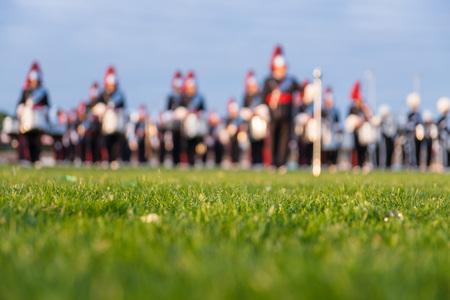 Details van een muziek-, show- en marcheband. Defocused achtergrond met gras en avond zon om te gebruiken als achtergrond