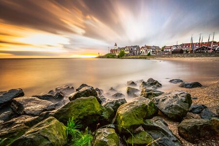 Lighthouse and village of the former Island of Urk alongside the lake IJsselmeer, long exposure with smooth water and dynamic sunset in the Netherlands