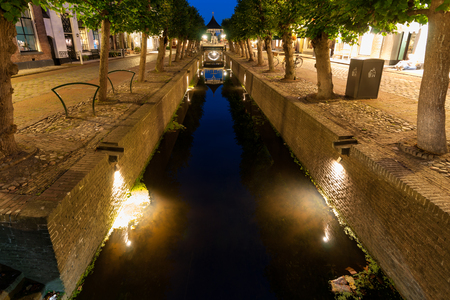 mirror image: The typical old Dutch city canals with reflections in the water. A long exposure shot at the blue hour after sunset. Stock Photo