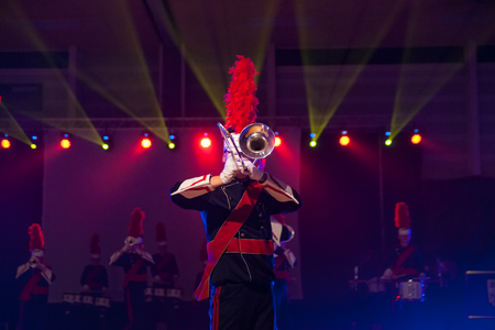 Details from a music, show and marching band. Playing musicians wind instruments in uniforms. Baritone, Mellofoon.
