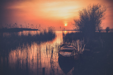 Old landscape with vintage rowing boat in a reed collar with atmospheric and intense sunset. Old pollard willows and drawn cloudy skies with sunbeams scorch the Dutch landscape with views over the lake.