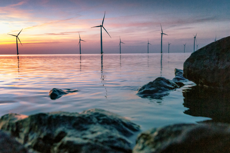 Romantic atmospheric sunset over the largest lake in the Netherlands (Ijsselmeer). Modern windmills stand in the water in a wind farm with a view from the dike and the basalt blocks of water protection.