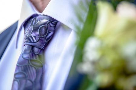 Cheerfully made up corsage with bright flowers. Groom with floral ornament for a wedding. Traditional wedding details for bride, brides sum and guests
